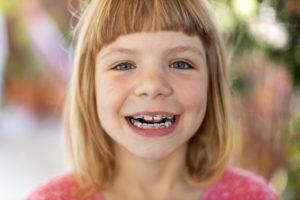 Young girl with braces smiles after visiting Randolph orthodontist