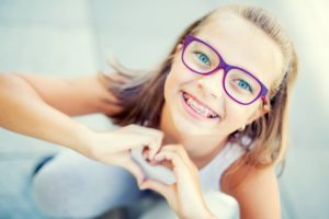 Young girl with braces making heart shape with hands after visiting Randolph orthodontist