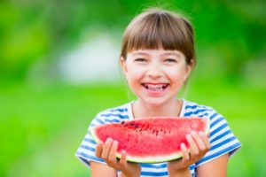 Girl with watermelon and braces in summer outside