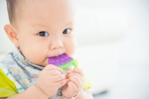 Young teething baby chewing on a teething toy