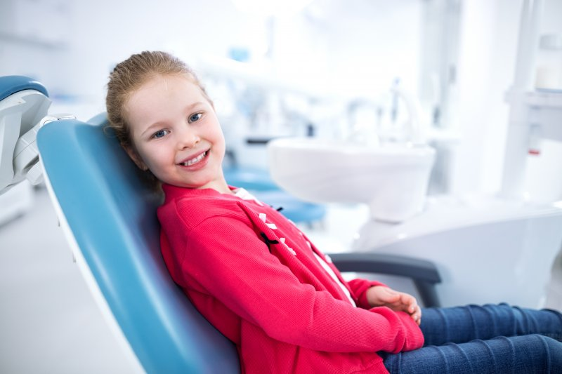 Child smiling while sitting in dentist's treatment chair