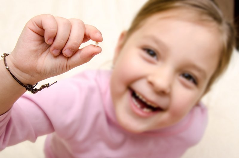 Closeup of little girl holding her baby tooth